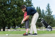 Father assisting his son to play golf in the course — Stock Photo