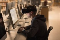 Teenage boy using virtual reality headset while studying in computer class at university — Stock Photo