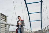 Young man walking on bridge while listening to music — Stock Photo