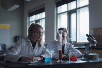 Estudiantes universitarios en experimento químico en laboratorio - foto de stock