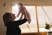 Mère jouant et soulevant bébé garçon à la maison . — Photo de stock