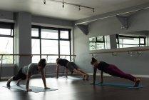 Treinador, auxiliando as pessoas na prática do yoga no estúdio de fitness. — Fotografia de Stock