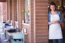 Femme à l'aide de téléphone portable à l'entrée du café — Photo de stock