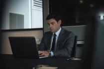 Uomo d'affari che utilizza il computer portatile alla scrivania in ufficio — Foto stock
