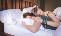 Coppia lesbica che dorme sul letto in camera da letto a casa . — Foto stock