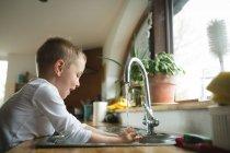 Мальчик мытья руки на кухню раковина дома — стоковое фото