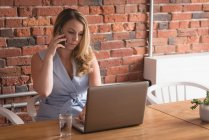 Female executive talking on mobile phone while using laptop in creative office — Stock Photo