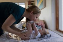 Feliz madre jugando con el bebé hijo en casa - foto de stock