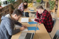 College students studying in library at university — Stock Photo