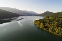 Vista panorámica del río pasando por bosques y montañas - foto de stock