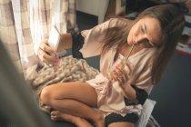 Frau in Nachtwäsche nehmen Selfie mit Handy bei Kaffee zu Hause. — Stockfoto