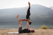 Вид сбоку на спортивных женщин, практикующих акро-йогу у морского побережья — стоковое фото
