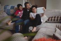Батько і діти мають Відеодзвінок на ноутбуці у вітальні на дому — стокове фото