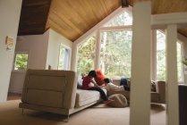 Fratelli e sorelle che utilizzano tablet digitale in soggiorno a casa — Foto stock