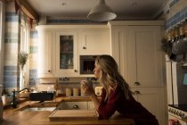 Young woman leaning on kitchen counter having coffee at kitchen — Stock Photo