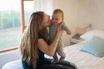 Мать переноски и целуя сына ребенок на кровати у себя дома — стоковое фото