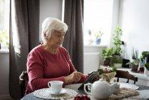 Mulher sênior usando tablet na sala de estar em casa — Fotografia de Stock