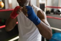 Mid section of senior man boxing in fitness studio. — Stock Photo