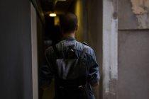 Вид сзади молодого человека ходить в коридоре здания — стоковое фото