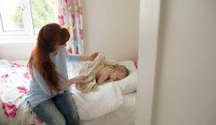 Мать убирает тело своей малышки с полотенцем дома — стоковое фото