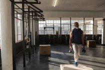 Uomo senior che si esercita con kettlebell in studio fitness determinato. — Foto stock
