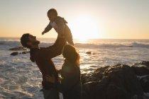 Сім'я, весело на пляжі під час заходу сонця — стокове фото