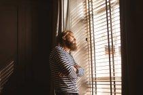 Вдумчивый человек смотрит из окна дома — стоковое фото