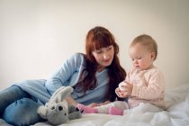 Mother and baby girl playing with toy in bedroom at home — Stock Photo