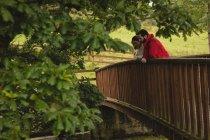 Coppia appoggiata sul ponte pedonale in campagna — Foto stock