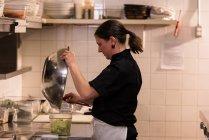 Poner la mezcla en un recipiente en la cocina del chef - foto de stock