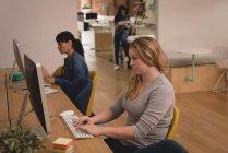 Femmes cadres travaillant sur ordinateur dans le bureau créatif — Photo de stock