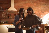 Friends having wine while preparing food in kicthen — Stock Photo