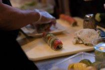 Koch rollt Sushi in Restaurantküche aus — Stockfoto