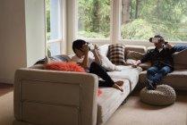 Père et fils utilisant casque de réalité virtuelle dans le salon à la maison — Photo de stock