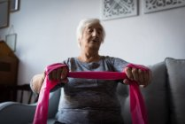Senior woman performing exercise with resistance band in living room at home — Stock Photo