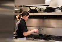 Cocinero mezcla la verdura en la sartén durante la cocción en la cocina comercial - foto de stock