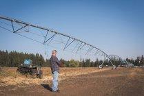 Фермер стоячи в поле на сонячний день — стокове фото