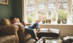 Человек, использующий мобильный телефон в кресле в гостиной на дому . — стоковое фото