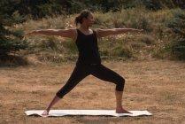 Подходящая женщина, выполняющая упражнения на растяжку на открытом воздухе в солнечный день — стоковое фото