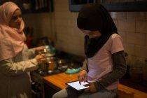 Muslimische Mutter kocht, während Tochter digitales Tablet in der Küche benutzt — Stockfoto