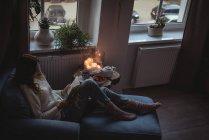 Высокий угол обзора женщины, читающей роман на кресле-кресле — стоковое фото