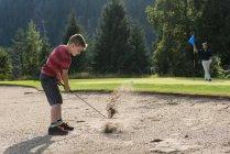 Chico tomando un trago en el campo de golf - foto de stock