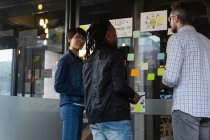 Executivos discutindo sobre notas pegajosas na parede de vidro no escritório . — Fotografia de Stock