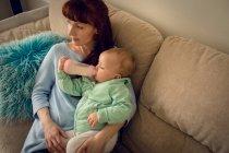 Малышка с матерью пьет молоко из детской бутылочки дома — стоковое фото