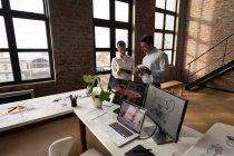 Geschäftspartner diskutieren im Büro über Design über digitales Tablet. — Stockfoto