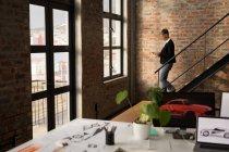 Donna d'affari che utilizza il telefono cellulare mentre scende le scale in ufficio . — Foto stock