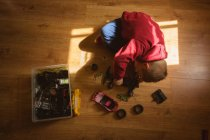 Little boy repairing toy car in bedroom at home — Stock Photo