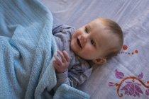 Крупный план счастливого ребенка, отдыхающего на кровати . — стоковое фото