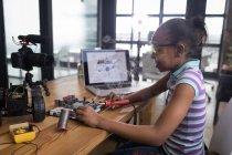 Подростковый блогер девушка паяльная плата электрическая игрушечная машина в офисе . — стоковое фото