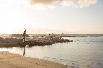 Человек идет на скале у моря во время заката — стоковое фото